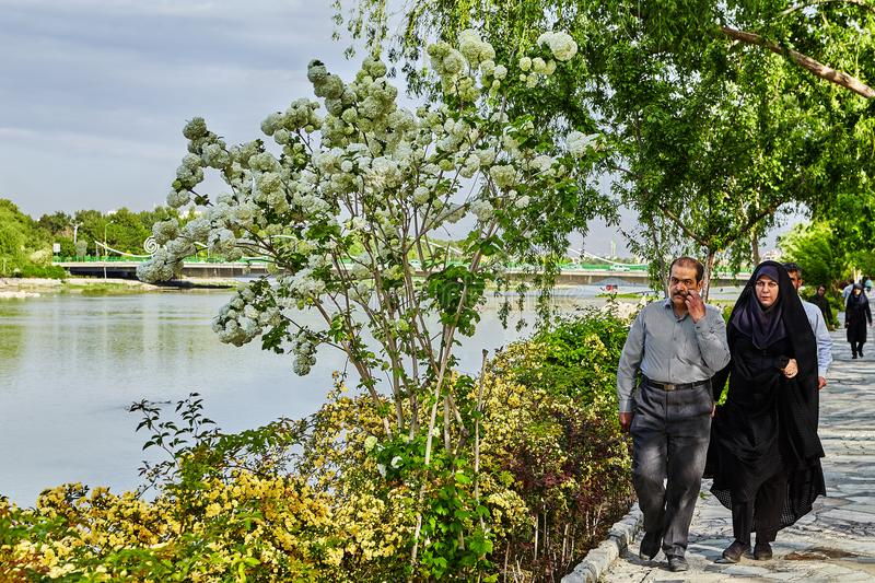 Iranian mature couple is walking along embankment of city river. royalty free stock photo