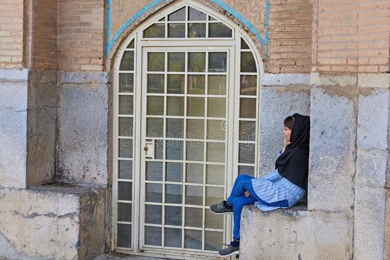Young Muslim woman talking on the phone, Isfahan, Iran. Isfahan, Iran - April 24, 2017: One young Iranian woman wearing a forced hijab, talking on the phone royalty free stock images