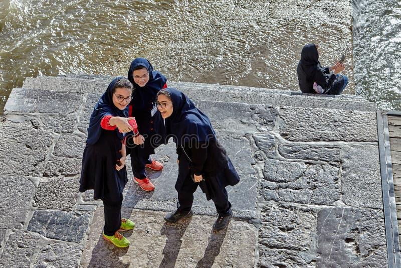 Iranian schoolgirls do selfie photo shoot near river, Isfahan, I royalty free stock photography