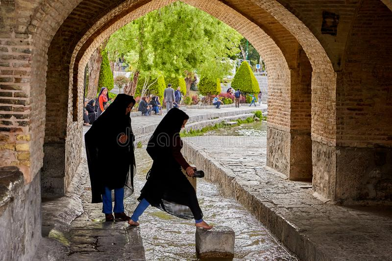 Young iranian women jump over water under bridge, Isfahan, Iran. royalty free stock images