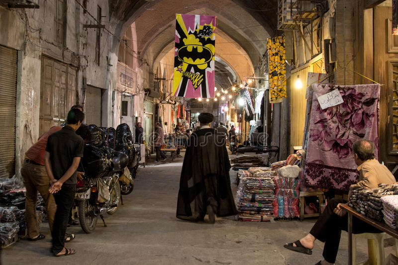 ISFAHAN, IRAN - AUGUST 20, 2016: Imam passing under a Batman logo in Isfahan bazaar. Picture of an Iranian imam from the back walking under a Batman logo, thus stock image