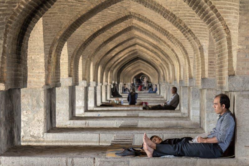 ISFAHAN IRAN, SIERPIEŃ, - 20, 2016: Irańscy ludzie odpoczywa pod łukami Khaju most w Isfahan, w ciepłych godzinach summ zdjęcie stock