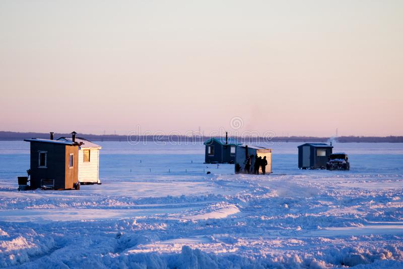Isfiskekojor och en bil på en djupfryst sjö arkivbilder