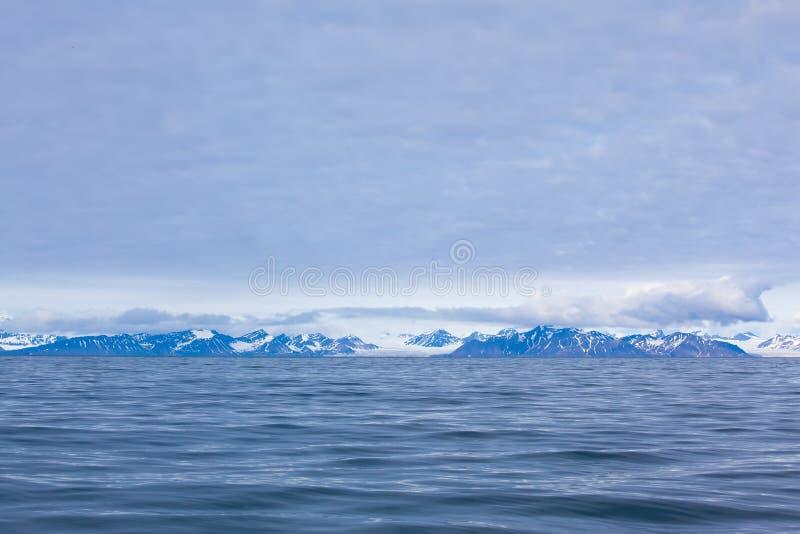Isfjord i Svalbard i Spitsbergen Härlig fjärd på bakgrunden av snöig berg royaltyfri bild