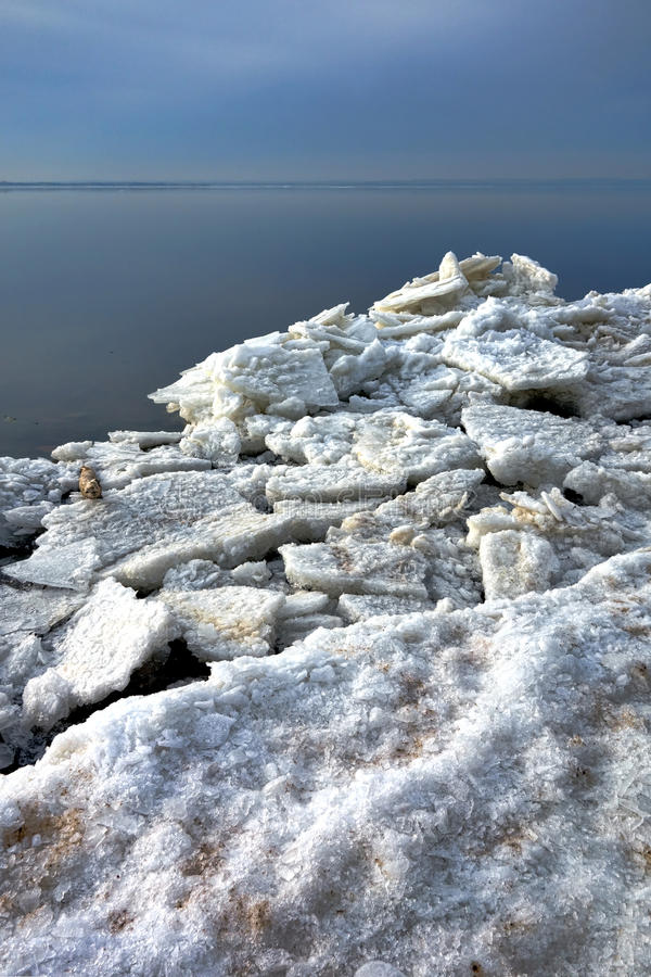 Isflötestora bitar och fryste stycken på vinterkust royaltyfri bild