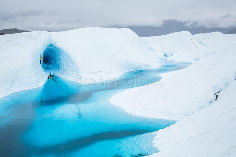 Isgrotta ovanför en stor blå sjö överst av den Matanuska glaciären i avlägsna Alaska Inom grottan leder en isklättrare ut ur royaltyfria foton