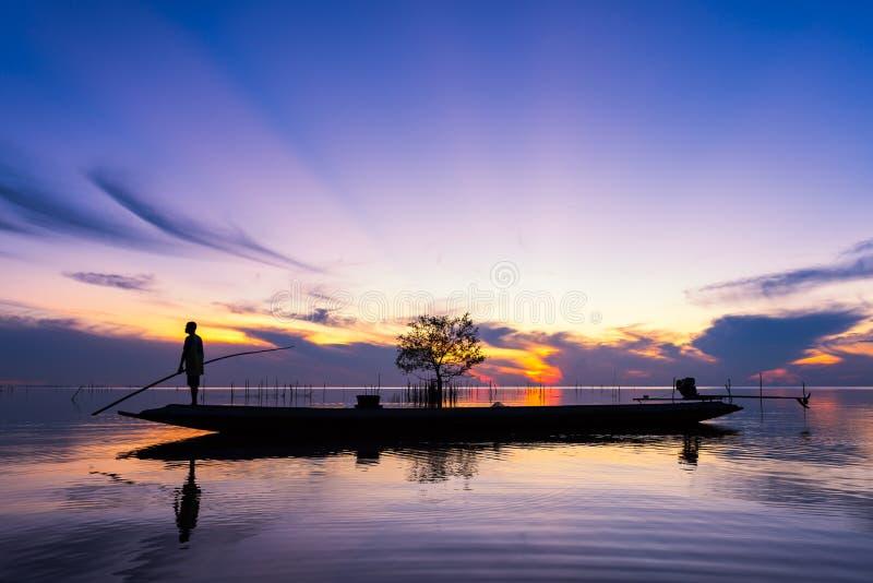 Isherman op lange staartboot in meer op zonsopgang bij Pakpra-dorp stock afbeeldingen