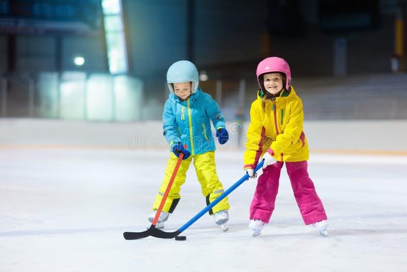 Ishockey för barnlek på inomhus isbana Sund vintersport för ungar Pojke och flicka med hockeypinnar som slår pucken barn arkivbilder