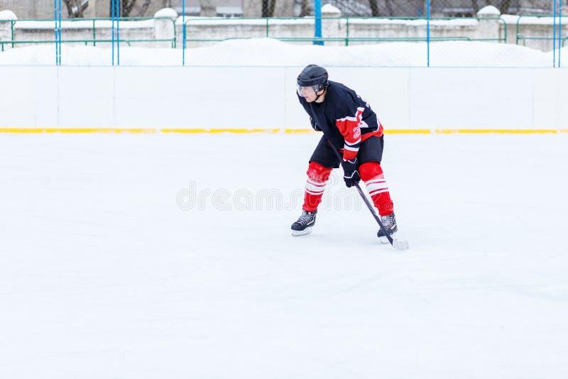 Ishockeyskateboradåkare med pinnen på isbana royaltyfria foton