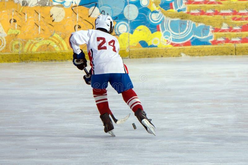 Ishockeyspelare i handling som sparkar med pinnen royaltyfri foto
