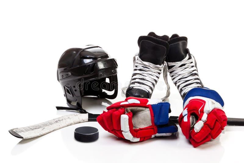 Ishockeyutrustning som isoleras på vit bakgrund arkivfoto