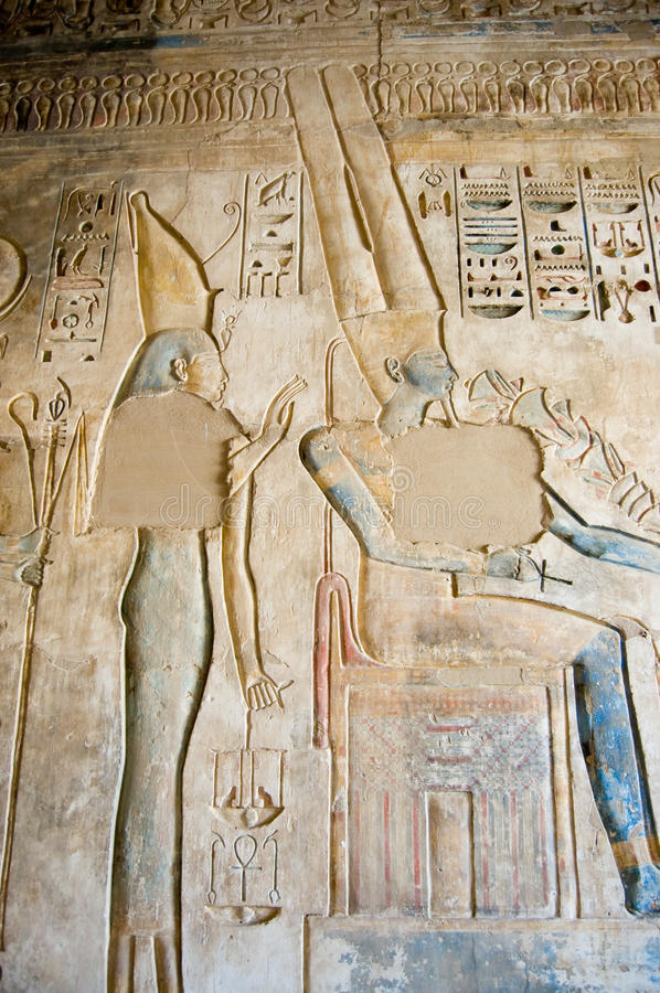 Isis and Amun Ancient Egyptian Hieroglyph. An Ancient Egyptian hieroglyphic carving showing the goddess Isis behind the seated king of the gods Amun Ra. This stock photography