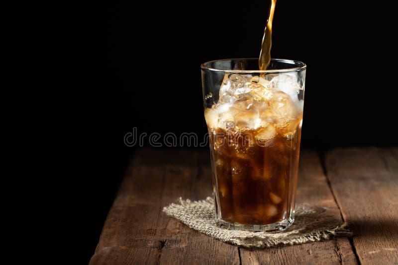Iskaffe i ett högväxt exponeringsglas över och kaffebönor på en gammal lantlig trätabell Kall sommardrink på en mörk bakgrund med fotografering för bildbyråer