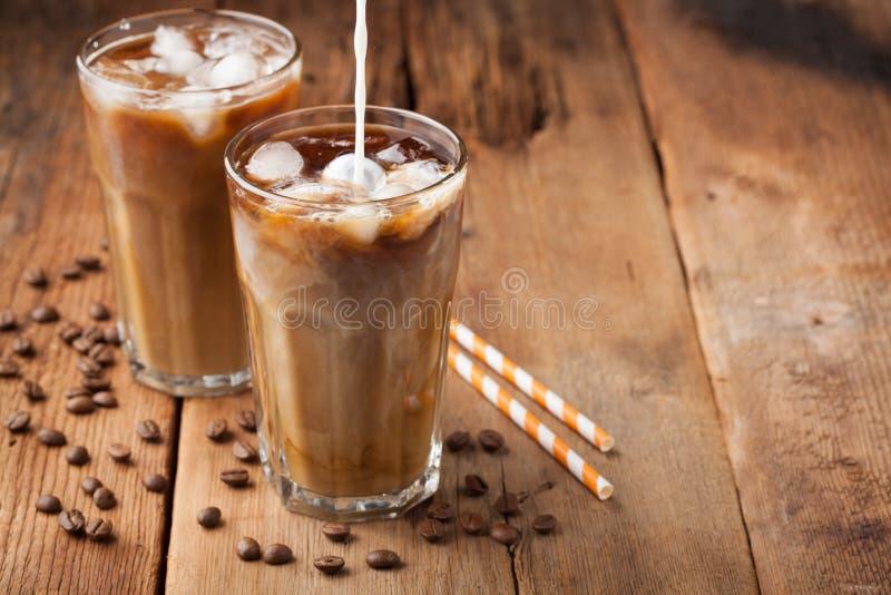 Iskaffe i ett högväxt exponeringsglas med kräm hällde över och kaffebönor på en gammal lantlig trätabell Kall sommardrink på en m fotografering för bildbyråer