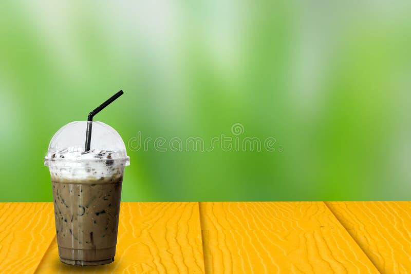 Iskaffe i plast- för tagande kopp bort med svart sugrör på den gula trätabellen på oskarp bakgrund för grön natur, kopieringsutry royaltyfria bilder