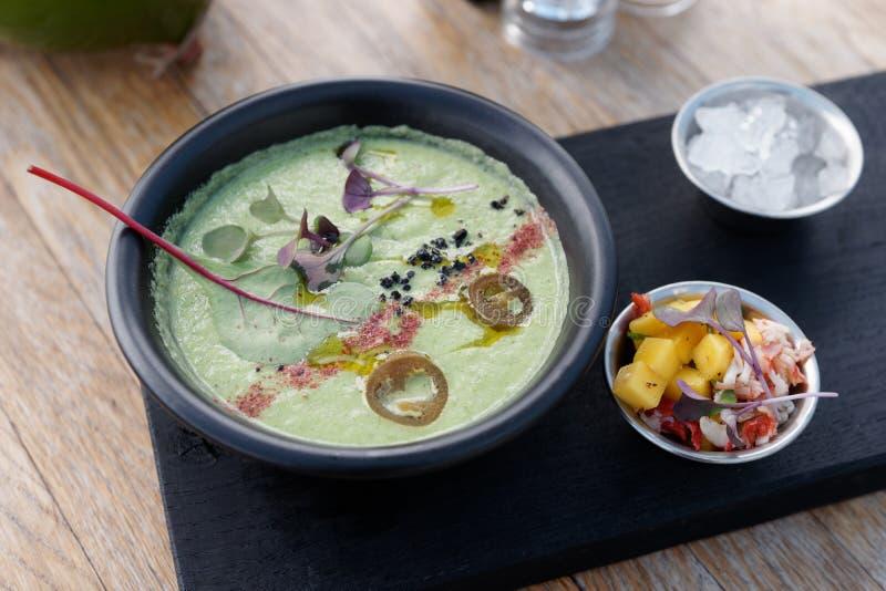 Iskall sommargrönsaksoppa med kryddor och foderbetabladet, krabban och mango royaltyfria foton