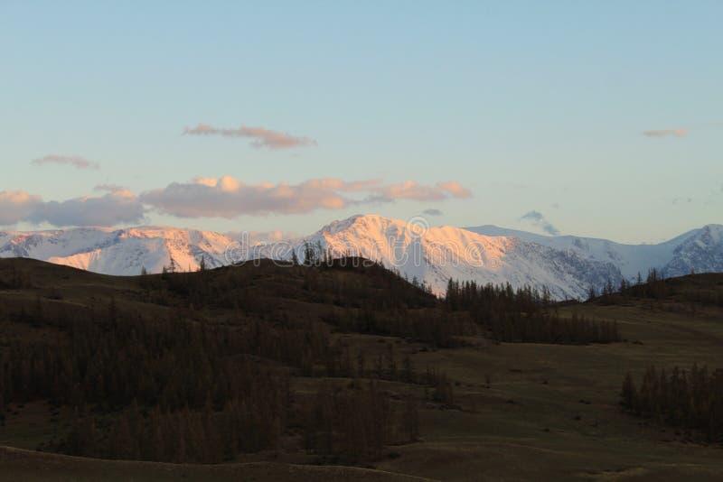 Iskalla berg i solnedgångljus royaltyfri bild