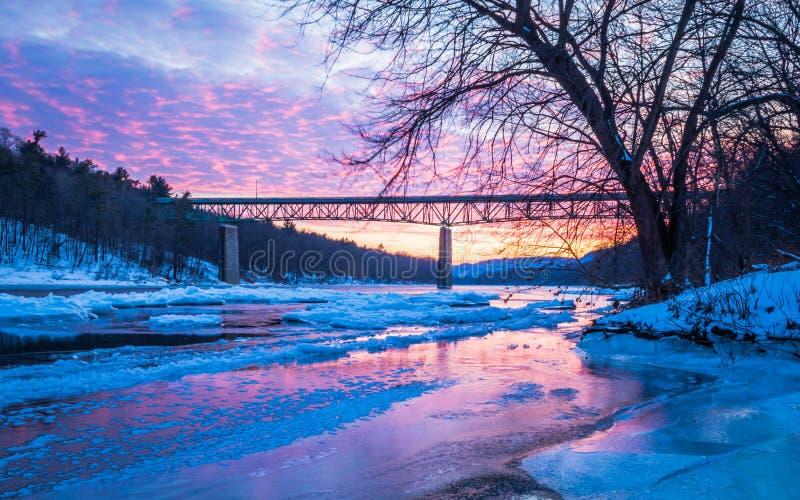 Iskalla Delaware River reflekterar den livliga solnedgången nära den Milford bron, PA fotografering för bildbyråer