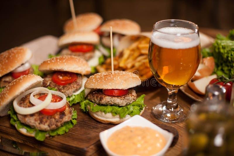 Iskallt öl med läckra hamburgare på en restaurangtabell arkivbild