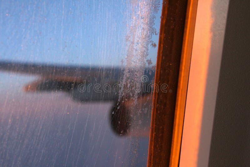 Iskallt flygplanfönster i flykten royaltyfri fotografi