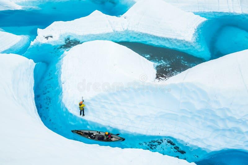 Isklättrare och en kanot nära en ö av is i en blå pöl på den Matanuska glaciären i Alaska royaltyfri foto