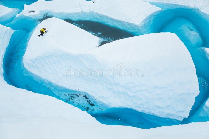 Isklättrare som soloing upp en ö av is som blickar som ett isberg i en stor blå pöl på den Matanuska glaciären royaltyfria bilder