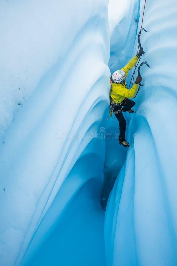 Isklättrare som trycker på hans baksida över den smala kanjonen av is på den Matanuska glaciären i Alaska royaltyfri fotografi