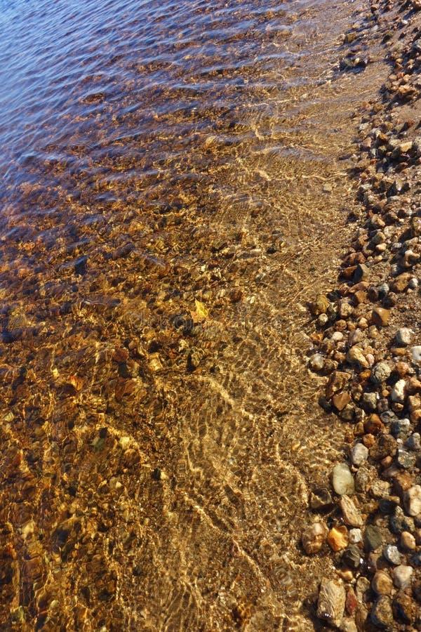 Iskrzasta czysta Maine jeziorna linia brzegowa z skałami pokazuje przez wody fotografia stock