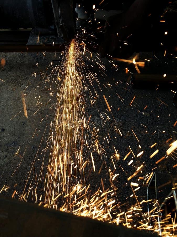 Iskrzyć światła podczas rozcięcia żelaza kawałka w parku przemysłowym fotografia stock