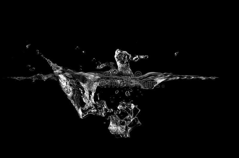 Iskub som faller i vatten över svart royaltyfri foto