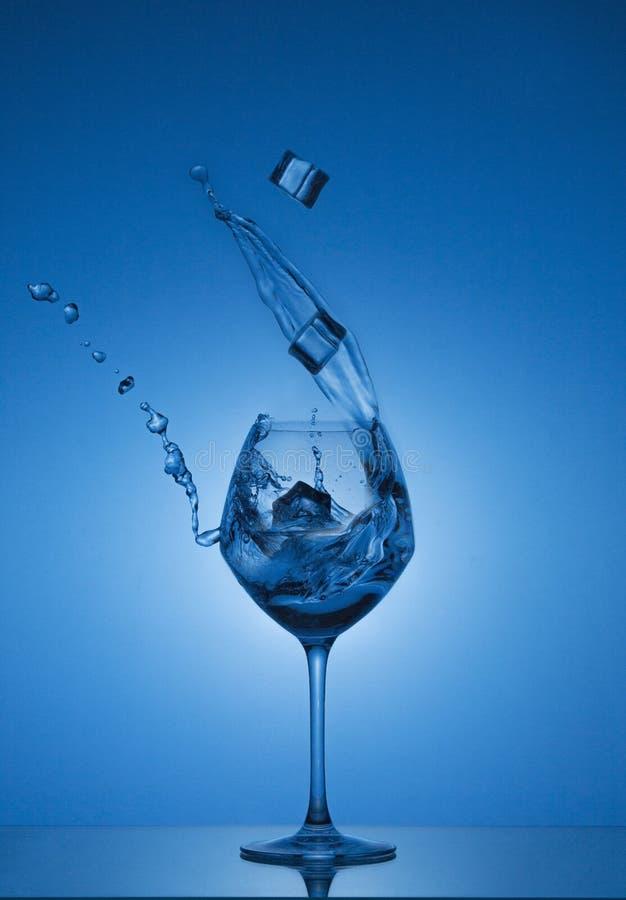 Iskuber faller in i ett exponeringsglas, och vatten hälls ut Vatten som plaskar ut ur ett högväxt vinexponeringsglas arkivbild