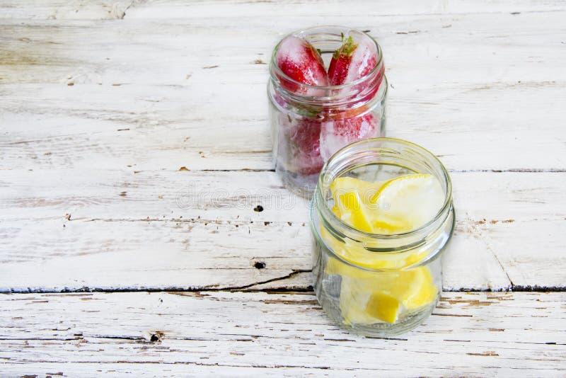 Iskuber med citroner och jordgubbar royaltyfri fotografi