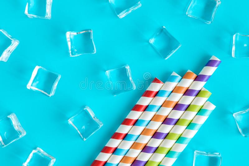 Iskuber och rev av mångfärgat abstrakt begrepp för dricka sugrör som isolerades på blått arkivfoton