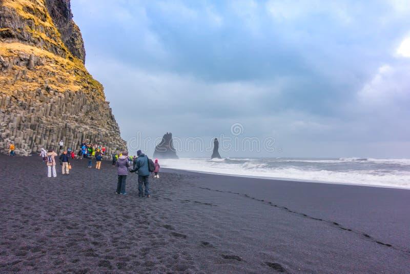 ISLÂNDIA - 15 de março - turista que aprecia na praia de Reynisfjara, sul imagens de stock