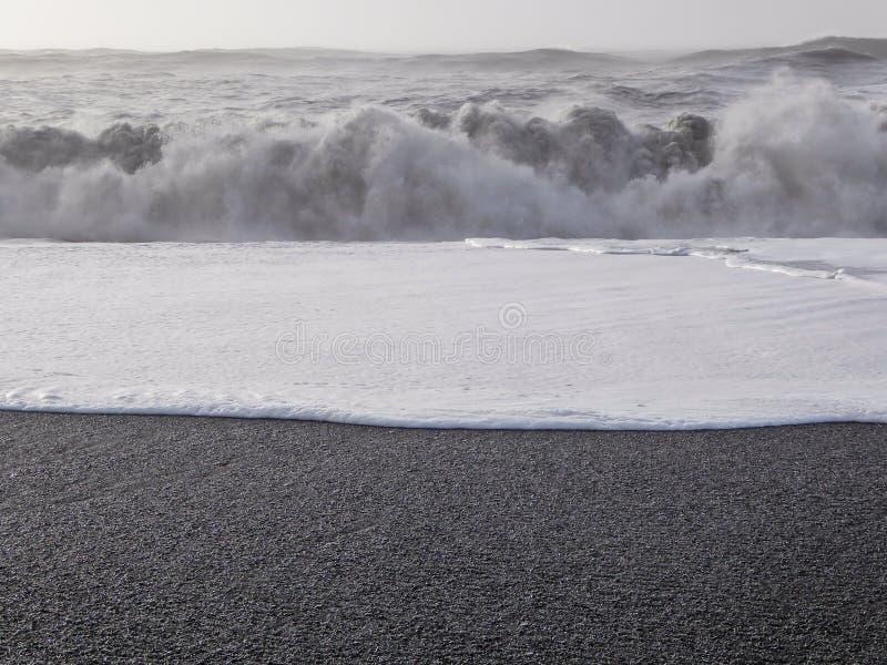 Islândia - praia preta da areia que mistura com a espuma branca das ondas foto de stock royalty free