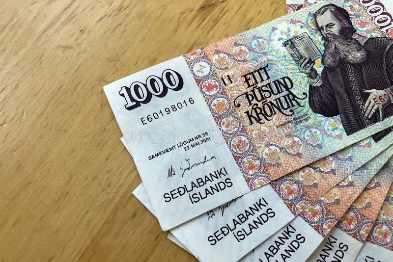 Isländsk kassa Pengar av Island Flera 1000 räkningar för isländsk krona på trätabellen Den isländska kronaen är den nationella va arkivbilder