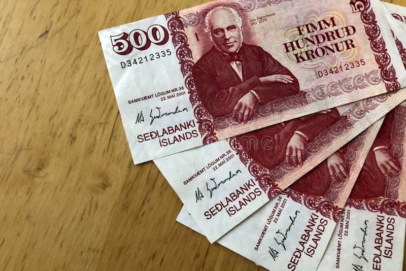 Isländsk kassa Pengar av Island Flera 500 räkningar för isländsk krona på trätabellen Den isländska kronaen är den nationella val royaltyfria foton