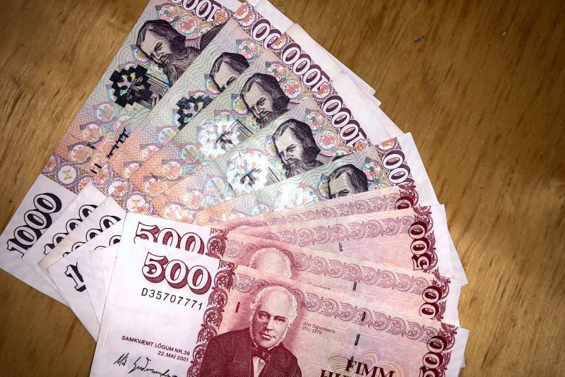 Isländsk kassa Pengar av Island Flera räkningar för isländsk krona på trätabellen Den isländska kronaen är den nationella valutan royaltyfria bilder