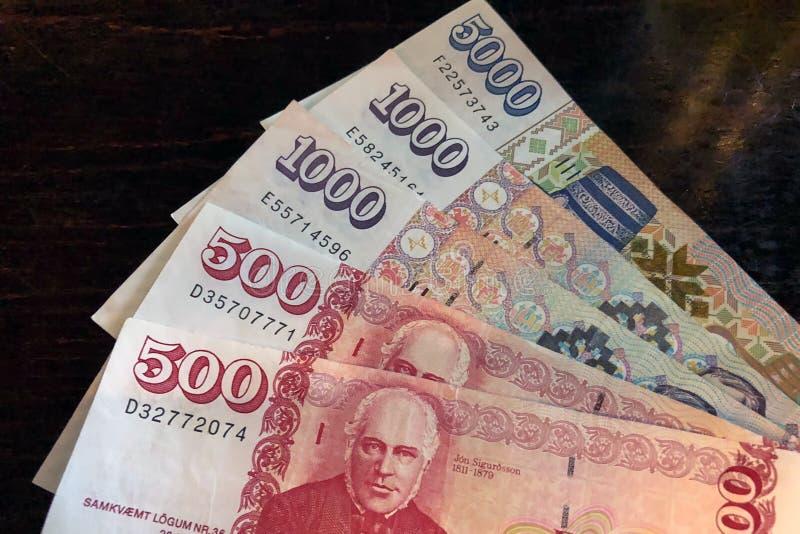 Isländsk kassa Pengar av Island Flera räkningar för isländsk krona på trätabellen Den isländska kronaen är den nationella valutan arkivbild