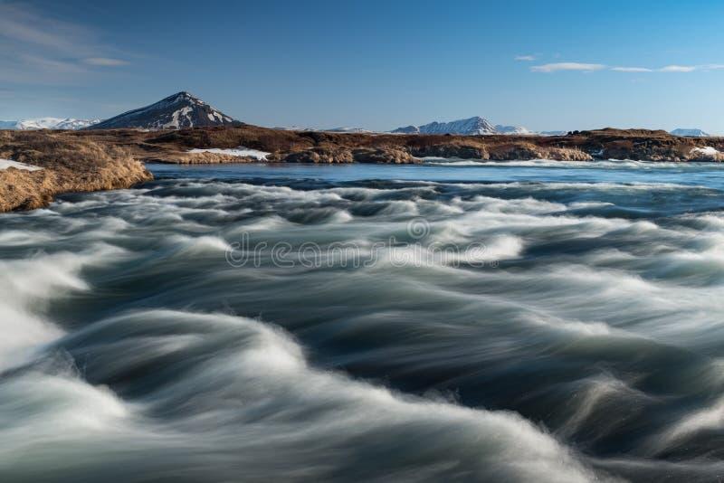Isländska flodvågor med en bergbakgrund royaltyfri foto