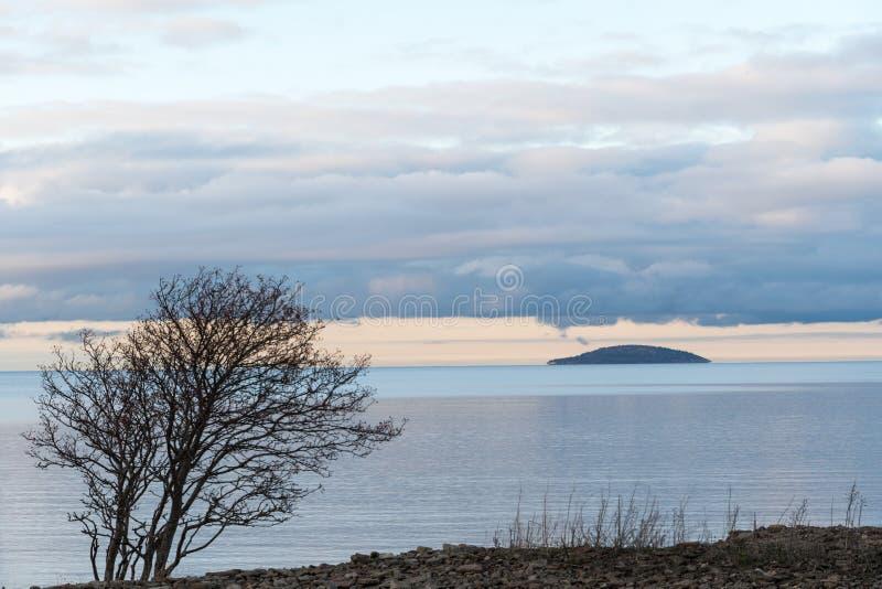 Isla azul de la soledad en agua tranquila foto de archivo