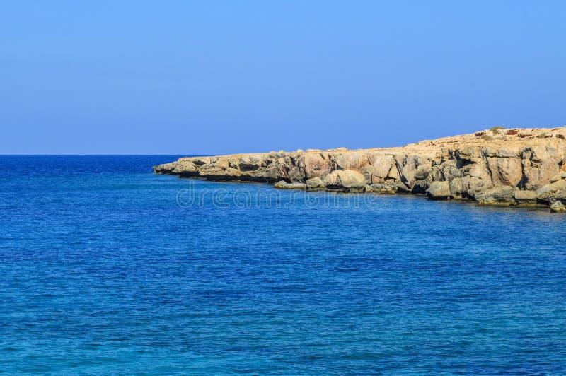 Isla de Chipre Costa costa mediterr?nea Día hermoso, cielo azul, ondas espumosas del rollo azul del mar a la orilla rocosa copia imagen de archivo