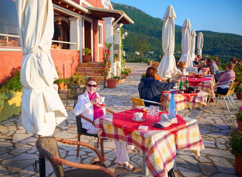 ISLA DE CORFÚ, GRECIA, EL 3 DE JUNIO DE 2014: La mujer bonita joven está cenando en café del restaurante del taverna del Griego c fotos de archivo libres de regalías