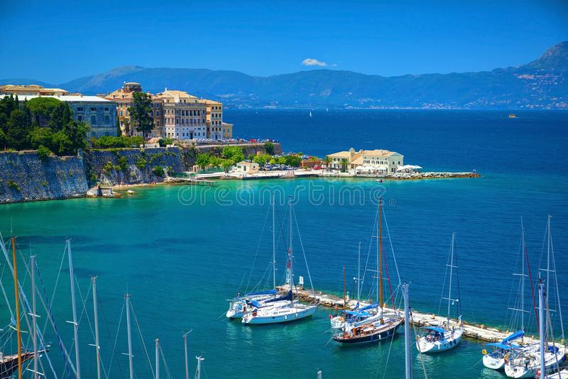 ISLA DE CORFÚ, GRECIA, JUNIO, 06, 2013: La opinión sobre los yates blancos clásicos hermosos se abriga, el puerto marítimo griego foto de archivo libre de regalías