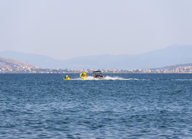 Isla de Evvoia, Grecia En julio de 2019: Los turistas nadan en el Mar Egeo en paseos inflables en la playa en un día de verano en imagenes de archivo