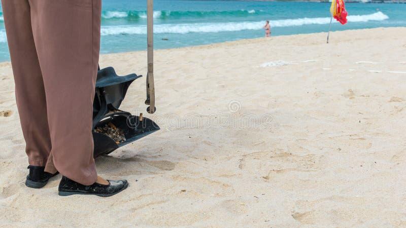 Isla de Hainan, Sanya, China - 16 de mayo de 2019: Una señora de la limpieza coge basura en la playa de Hainan con el fórceps prá foto de archivo