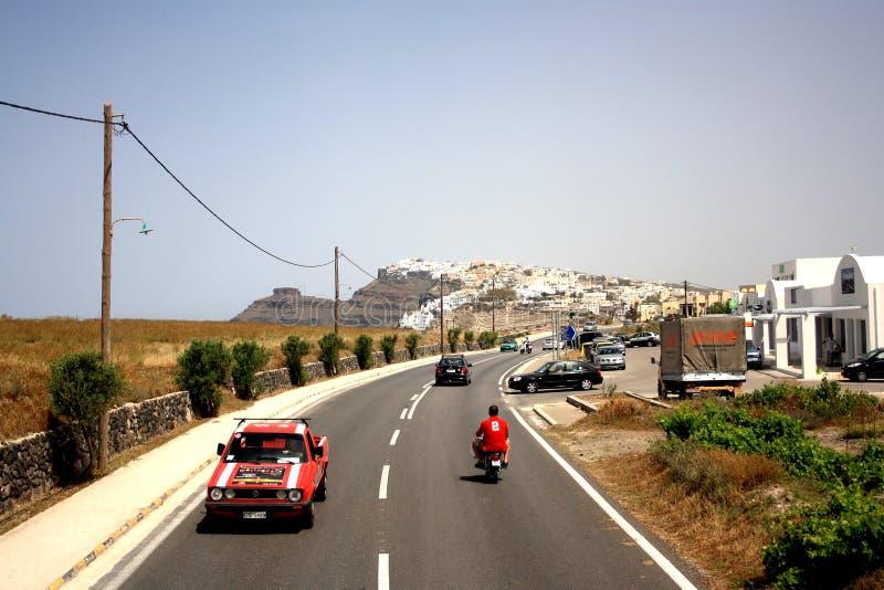Isla de Santorini, Grecia - 5 de mayo de 2013: Un camino en la isla con un coche rojo y un hombre en el motocycle imagenes de archivo
