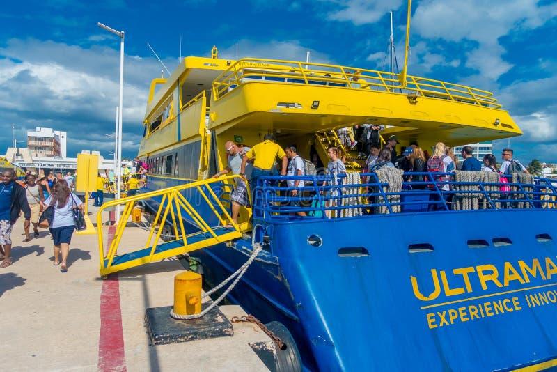ISLA MUJERES, MÉXICO, O 10 DE JANEIRO DE 2018: Povos não identificados que embarcam um barco enorme da cor azul e amarelo para vi imagens de stock royalty free