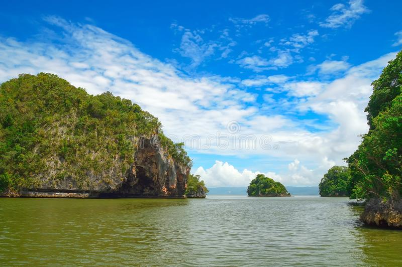Isla, roca en el Océano Atlántico cubierto con la vegetación verde, contra un contexto de la orilla en el fondo Los foto de archivo libre de regalías