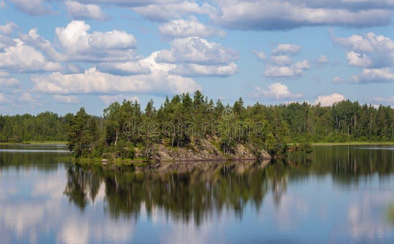 Isla rocosa y su reflexión fotos de archivo